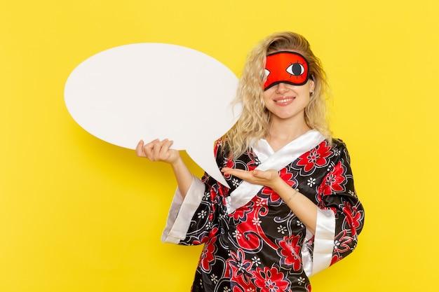 Giovane femmina di vista frontale in abito da notte che tiene un enorme cartello bianco con il sorriso sul colore della ragazza del modello del letto di notte di sonno della parete gialla chiara