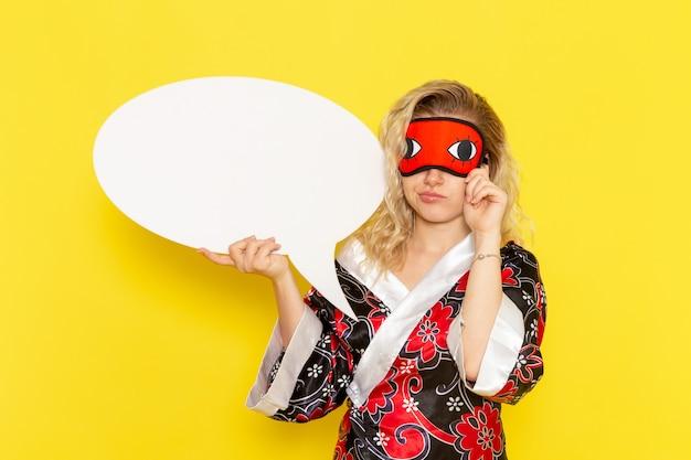 Vista frontale giovane femmina in abito da notte con enorme cartello bianco sul muro giallo dormire notte letto modello ragazza colore