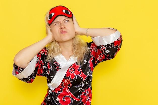 Vista frontale giovane femmina in abito da notte e indossa la maschera per gli occhi chiudendo le orecchie sul muro giallo dormire ragazza notte letto modello