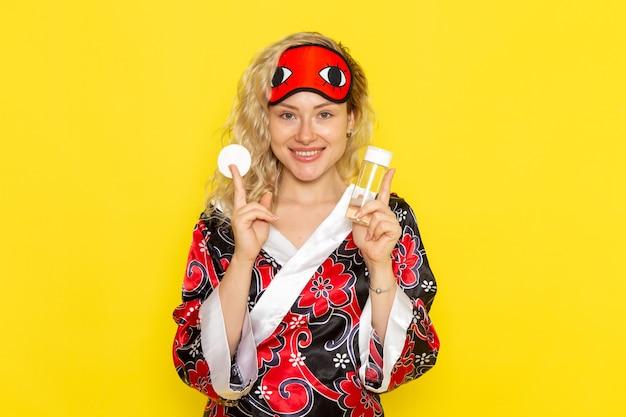 Giovane donna di vista frontale in abito da notte e maschera per gli occhi che indossa la boccetta per la rimozione del trucco sul modello di letto notturno della ragazza di sonno della scrivania gialla