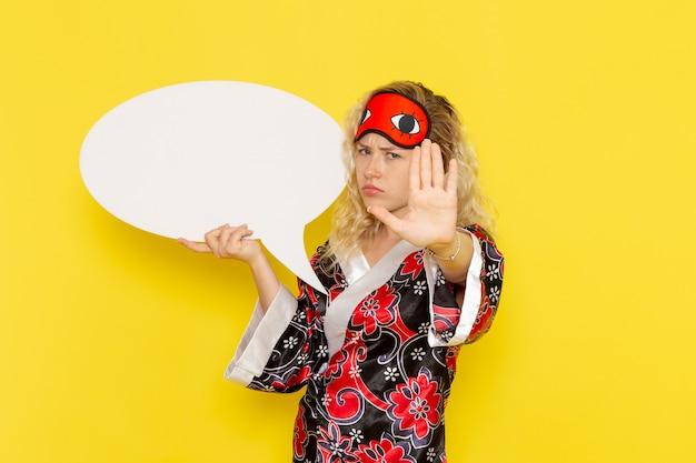 Giovane donna di vista frontale in abito da notte e maschera per gli occhi con indosso un enorme cartello bianco sul colore della ragazza del modello del letto di notte di sonno della parete gialla chiara