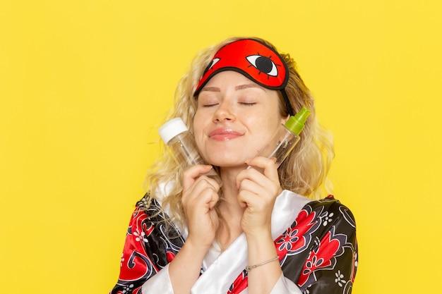 Vista frontale giovane donna in abito da notte e indossa una maschera per gli occhi si prepara a dormire tenendo la boccetta e lo spray sulla scrivania gialla dormire modello femminile letto notturno