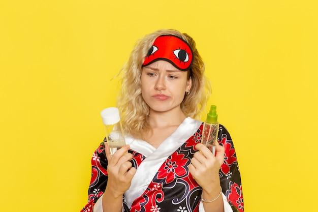 Vista frontale giovane donna in abito da notte e indossa una maschera per gli occhi si prepara a dormire tenendo la boccetta e lo spray sul muro giallo dormire modello femminile letto notturno