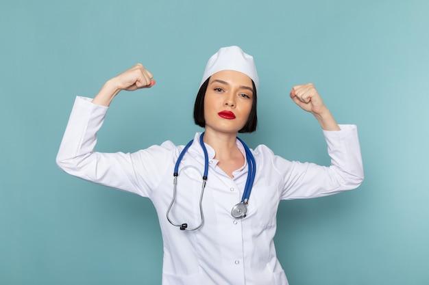 Una giovane infermiera femminile di vista frontale in tuta medica bianca e flessione stetoscopio blu