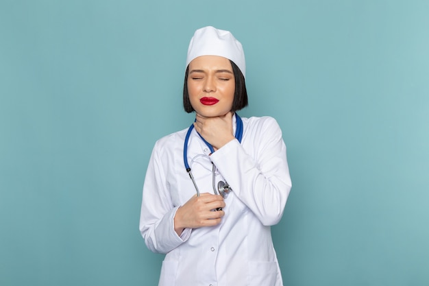 A front view young female nurse in white medical suit and blue stethoscope having throat issues