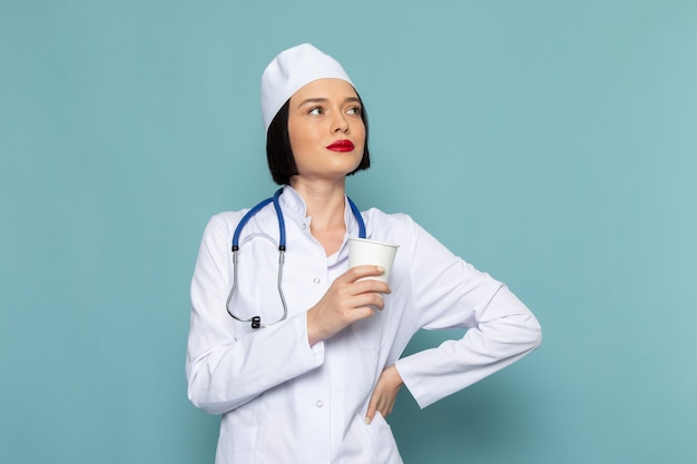 A front view young female nurse in white medical suit and blue stethoscope holding plastic glass on the blue desk medicine hospital doctor