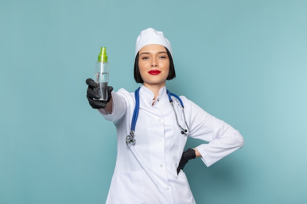 A front view young female nurse in white medical suit and blue stethoscope holding spray flask on the blue desk medicine hospital doctor