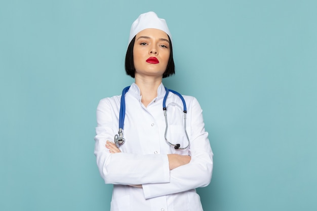 A front view young female nurse in white medical suit and blue stethoscope posing on the blue desk medicine hospital doctor