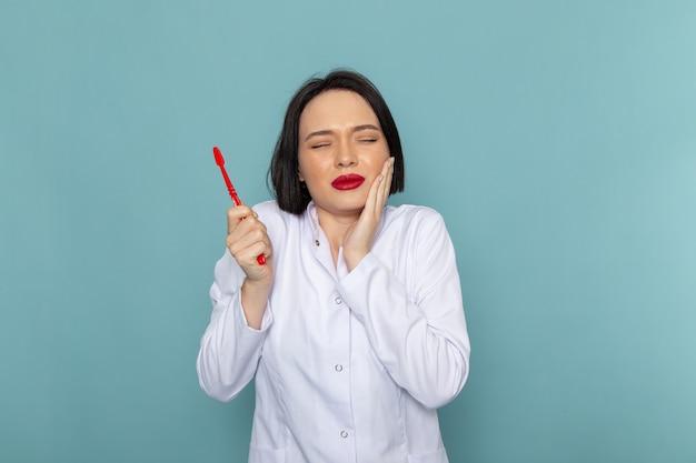 Una giovane infermiera femminile di vista frontale in vestito medico bianco che ha un mal di denti sul medico dell'ospedale della medicina dello scrittorio blu