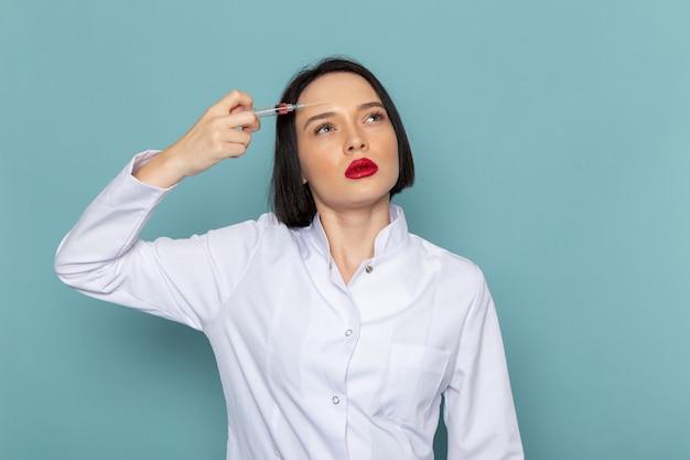 Una giovane infermiera femminile di vista frontale in vestito medico bianco injectiong se stessa sul medico dell'ospedale della medicina dello scrittorio blu