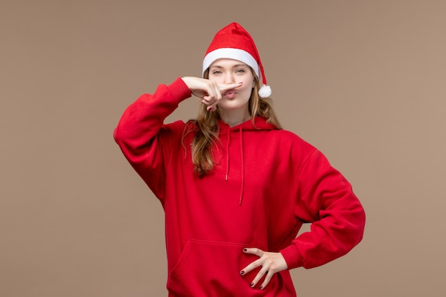 Вид спереди молодая женщина на коричневом фоне рождественские эмоции праздник