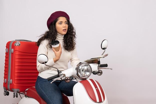 Вид спереди молодая женщина на велосипеде, держащая карту и кофе на белом фоне, цветная дорога города, скорость автомобиля, отпуск