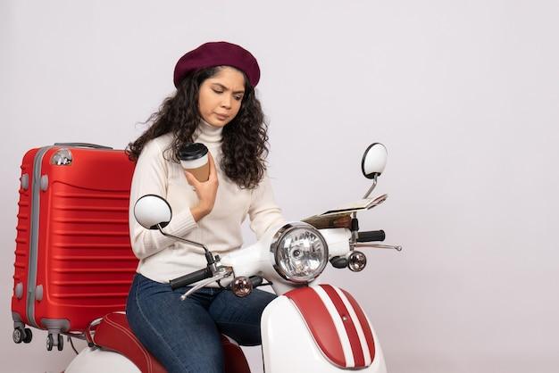 Вид спереди молодая женщина на велосипеде, держащая карту и кофе на белом фоне, цвет города, дорожный транспорт, скорость мотоцикла