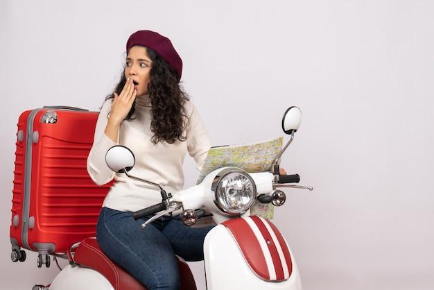 Вид спереди молодая женщина на велосипеде, держащая карту на белом фоне, цвет города, дорога, отпуск, автомобиль, скорость езды