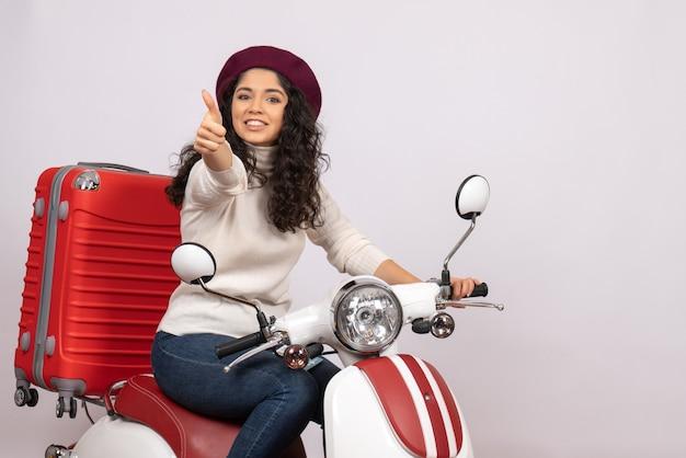 Вид спереди молодая женщина на велосипеде со своей сумкой, улыбаясь на белом фоне, цветная поездка, скорость, скорость, мотоцикл, отпускное транспортное средство