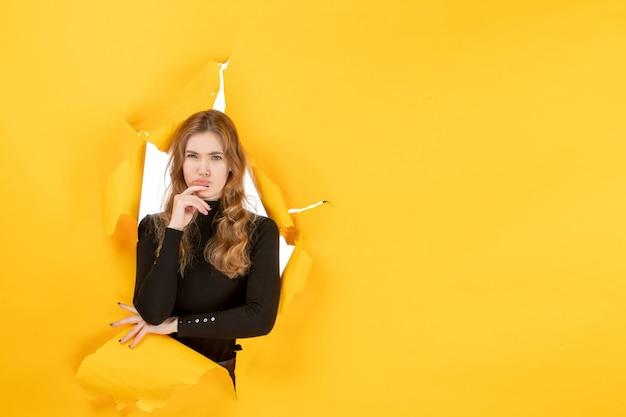 노란색 찢어진 된 벽에 전면보기 젊은 여성