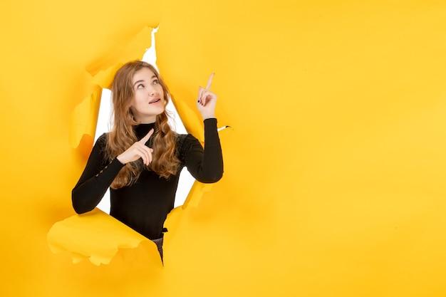 黄色の破れた壁の正面図若い女性
