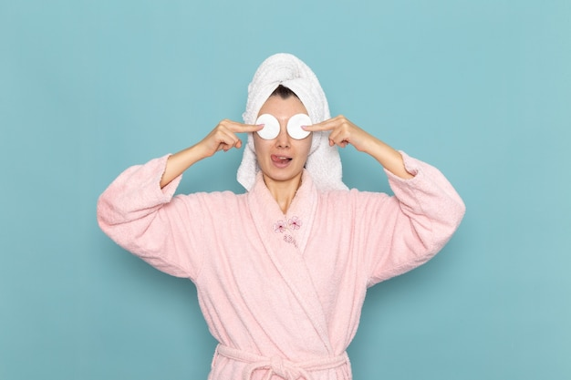 Front view young female in pink bathrobe after shower covering her eyes with cotton on light-blue wall beauty water selfcare shower clean
