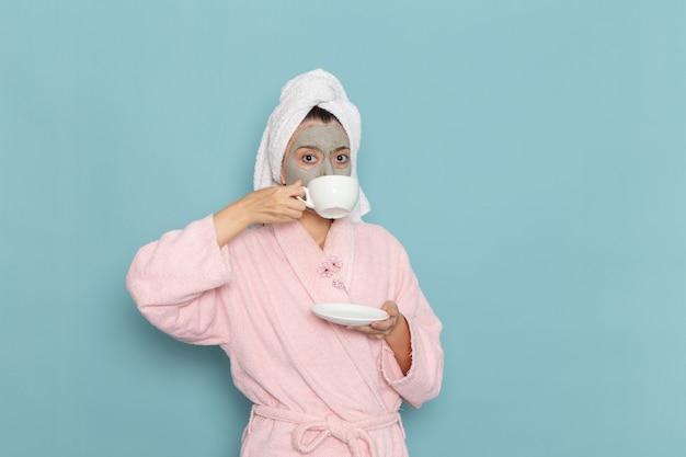 Giovane donna di vista frontale in accappatoio rosa dopo la doccia che beve caffè sulla doccia di auto-cura di bellezza della parete azzurra