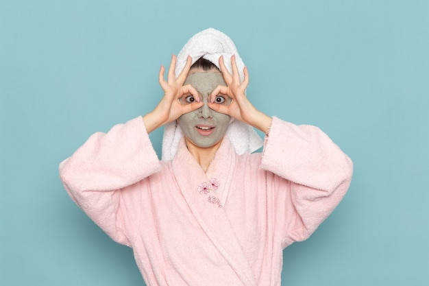 Front view young female in pink bathrobe after shower funny posing on blue wall cleaning beauty clean water selfcare cream shower