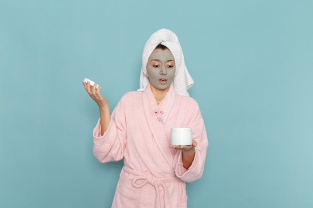Front view young female in pink bathrobe after shower holding cream on the blue wall beauty water bath cream selfcare shower bathroom