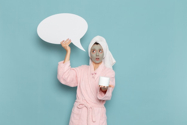 Front view young female in pink bathrobe after shower holding cream and sign on blue wall beauty water cream selfcare shower bathroom