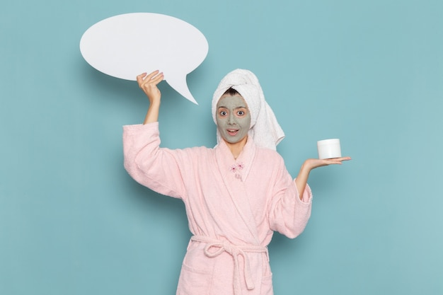 Front view young female in pink bathrobe after shower holding huge white sign on blue desk beauty water cream selfcare shower bathroom
