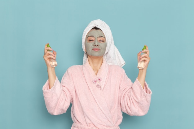 Front view young female in pink bathrobe after shower holding make-up removers on blue wall beauty water cream selfcare shower