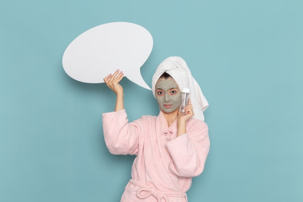 Front view young female in pink bathrobe after shower holding sign and spray on the blue wall beauty water cream selfcare shower bathroom