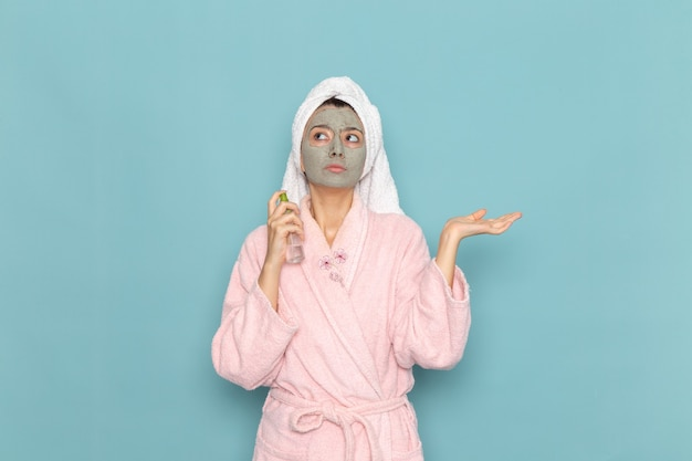 Giovane femmina di vista frontale in accappatoio rosa dopo doccia che tiene spray sulla parete blu pulizia bellezza acqua pulita doccia crema selfcare