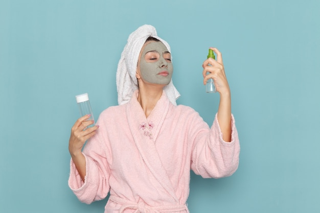 Front view young female in pink bathrobe after shower holding sprays on blue wall beauty water bath cream selfcare shower