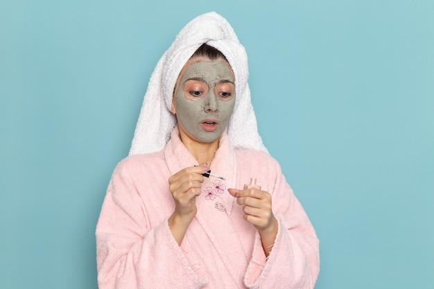 Giovane femmina di vista frontale in accappatoio rosa dopo la doccia sulla doccia di auto-cura dell'acqua pulita di bellezza della parete azzurra