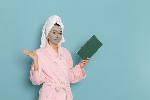 Front view young female in pink bathrobe after shower reading copybook on the blue wall beauty water bath cream selfcare shower bathroom