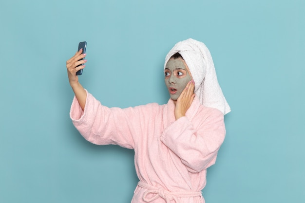 Front view young female in pink bathrobe after shower taking selfie on light-blue wall beauty water selfcare shower clean