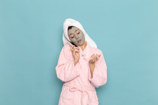 Giovane femmina di vista frontale in accappatoio rosa dopo la doccia che parla al telefono sulla doccia di auto-cura dell'acqua di bellezza della parete azzurra pulita