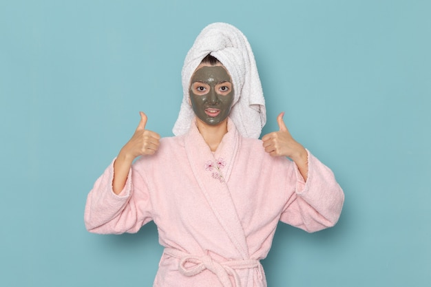 Giovane donna di vista frontale in accappatoio rosa dopo la doccia con la maschera scura sul viso sulla scrivania blu bellezza acqua crema selfcare doccia bagno