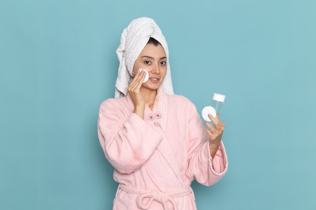 Front view young female in pink bathrobe cleaning her face from make-up on blue desk cleaning beauty selfcare cream shower
