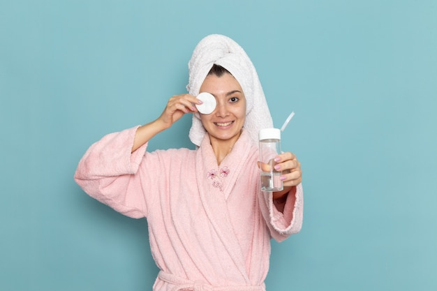 Front view young female in pink bathrobe cleaning her face from make-up on blue floor cleaning beauty selfcare cream shower