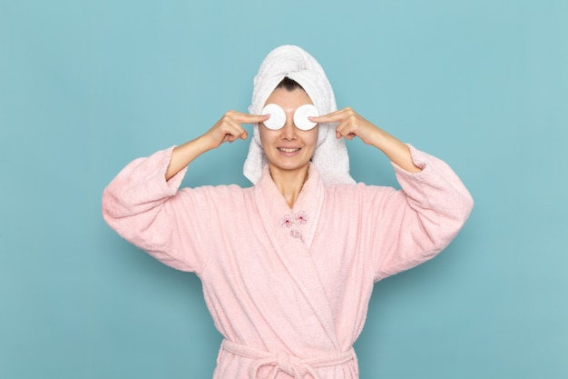 Giovane femmina di vista frontale in accappatoio rosa che copre gli occhi con poco cotone sulla crema di selfcare di bellezza di pulizia della doccia della parete blu