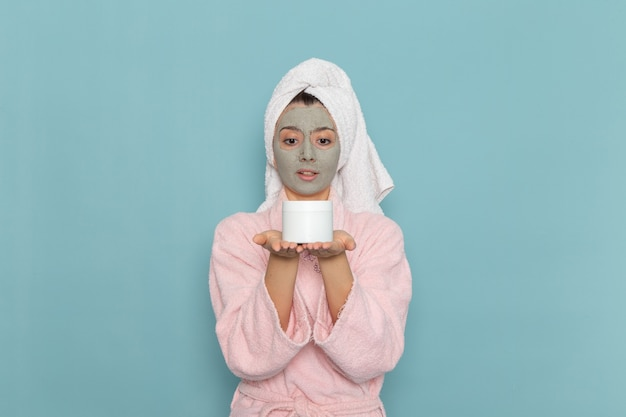 Giovane femmina di vista frontale in accappatoio rosa che tiene crema sulla crema di auto-cura di bellezza di pulizia della doccia della parete blu-chiaro
