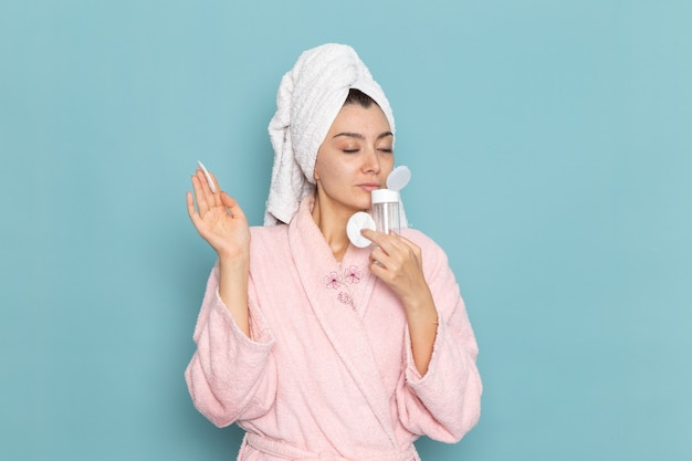 Front view young female in pink bathrobe holding make-up remover on blue wall cleaning beauty clean water selfcare cream shower