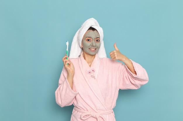 Giovane femmina di vista frontale in accappatoio rosa che tiene lo spazzolino da denti sulla doccia blu della crema di auto-cura di bellezza di pulizia della parete blu