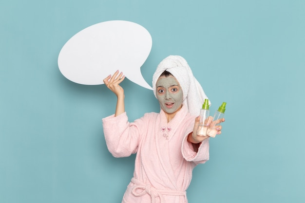 Giovane femmina di vista frontale in accappatoio rosa che tiene segno bianco e spruzza sulla doccia di auto-cura della crema del bagno di acqua di bellezza della parete blu
