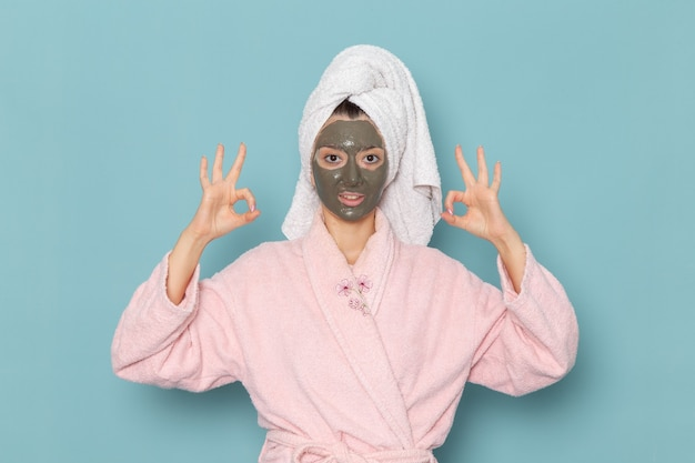Giovane femmina di vista frontale in accappatoio rosa che posa con la maschera sul viso sulla doccia di auto-cura di crema da bagno d'acqua bellezza parete blu