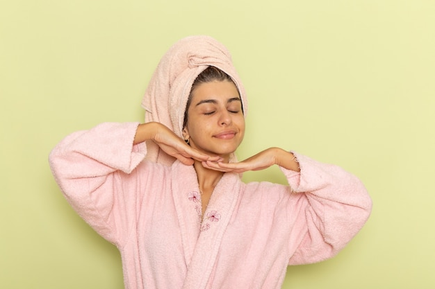Front view young female in pink bathrobe posing and smiling on a green surface