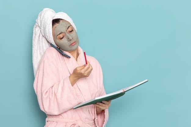 Giovane femmina di vista frontale in accappatoio rosa che parla sul telefono sulla doccia crema di selfcare di bellezza di pulizia della parete blu