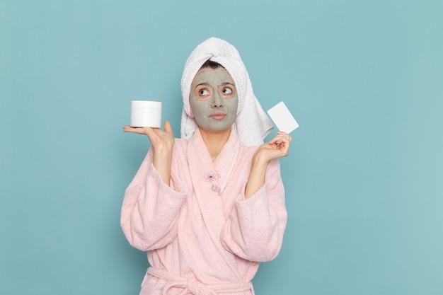 Giovane femmina di vista frontale in accappatoio rosa con la maschera sulla sua carta della tenuta del fronte sulla crema di auto-cura di bellezza di pulizia della doccia della parete blu