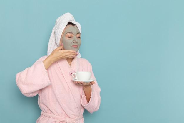 Giovane femmina di vista frontale in accappatoio rosa con la maschera sul suo fronte che tiene il caffè sulla crema di selfcare di bellezza di pulizia della doccia della parete blu