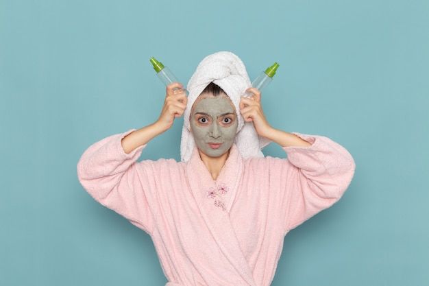 Giovane femmina di vista frontale in accappatoio rosa con la maschera sul suo viso che tiene gli spruzzi sulla crema di selfcare di bellezza di pulizia della doccia della parete blu