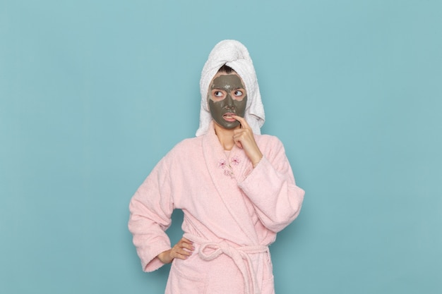 Front view young female in pink bathrobe with mask on her face thinking on the blue wall shower cleaning beauty selfcare cream